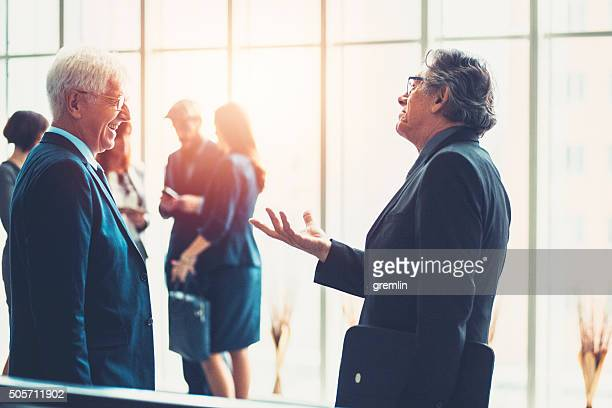 Two senior adult businessmen talking in the lobby