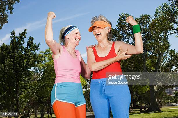 Two senior adult women exercising in park