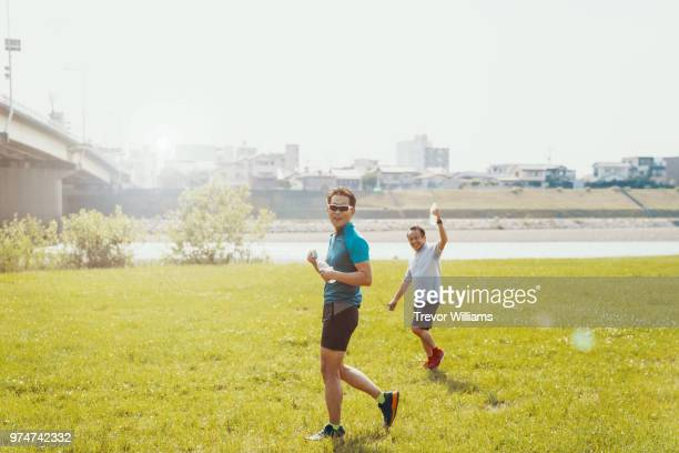 two senior adults drinking water after jogging or running together - 気が若い ストックフォトと画像
