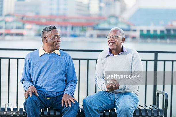Two senior African American men on bench by waterfront