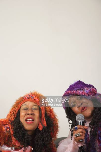two senior african women singing - eccentric stock pictures, royalty-free photos & images