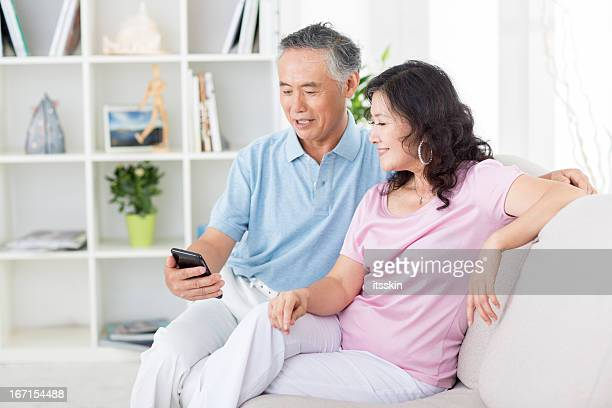 Two senior asian people looking at mobile phone