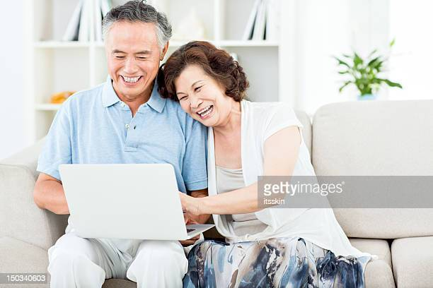 Two senior asian people using computer