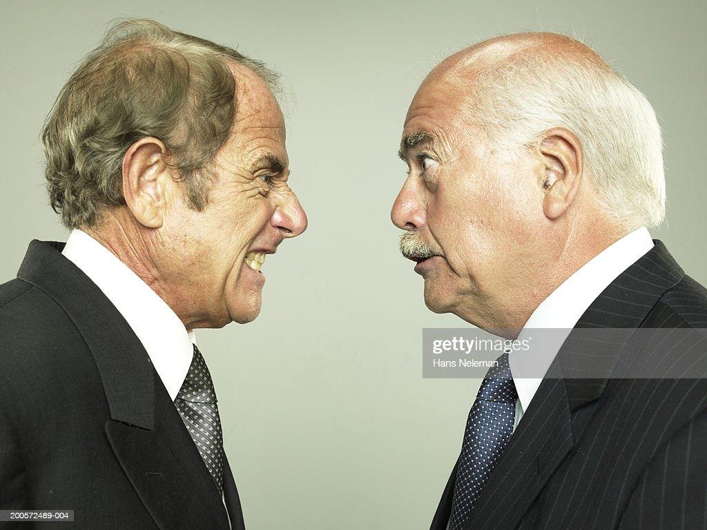 Two senior business men face to face, yelling, studio shot : Stock Photo