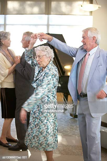 Two senior couples dancing around piano