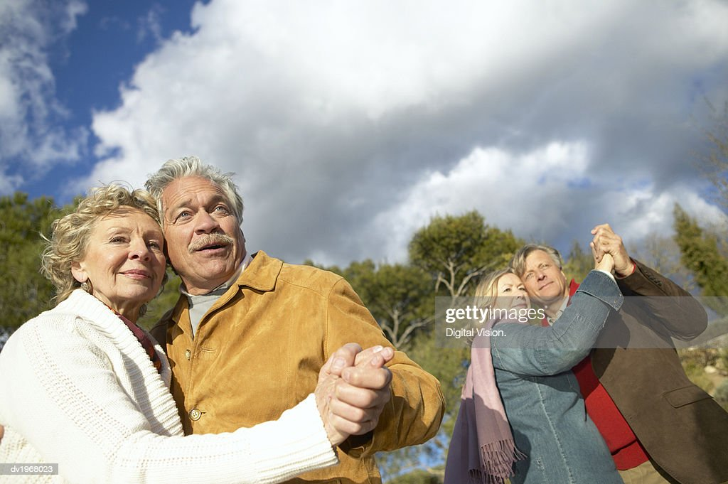 Two Senior Couples Dancing Together Outdoors : Stock Photo