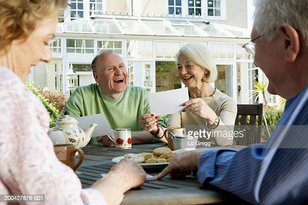 Two senior couples looking at photographs around garden table, smiling