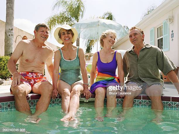 Two senior couples sitting at side of pool, smiling