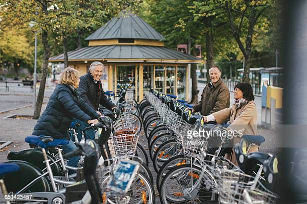 two senior couples taking rental bikes at parking lot - bicycle parking station stock photos and pictures