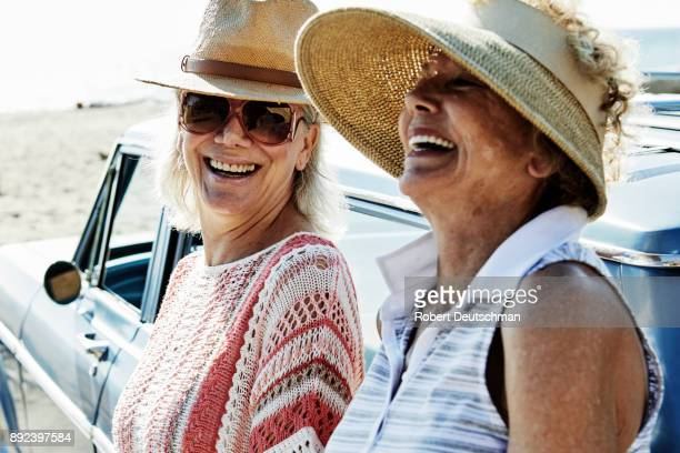 Two senior female friends hanging out together on a road trip to the beach