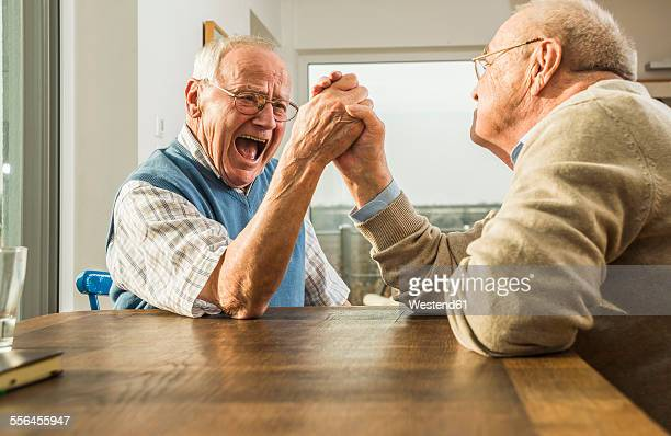 two senior friends arm wrestling - young at heart stock pictures, royalty-free photos & images