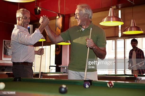 Two senior friends celebrating pool shot