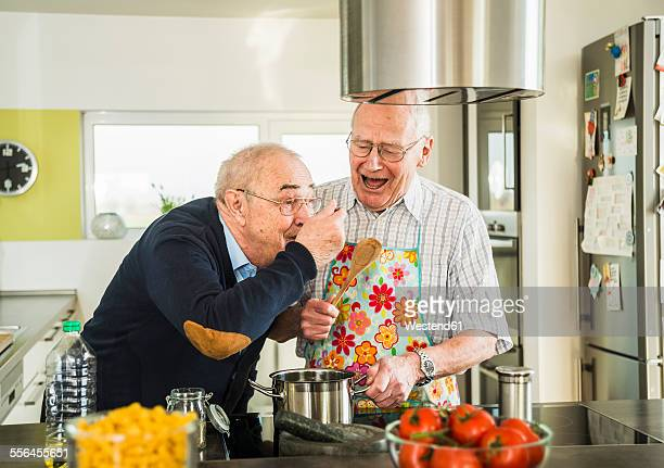 Two senior friends cooking in kitchen