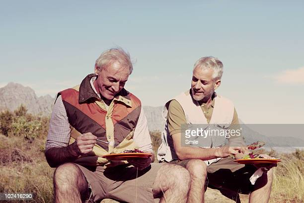 Two senior friends eating in the wilderness