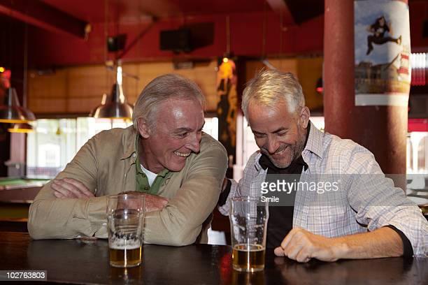 Two senior friends having a laugh in bar