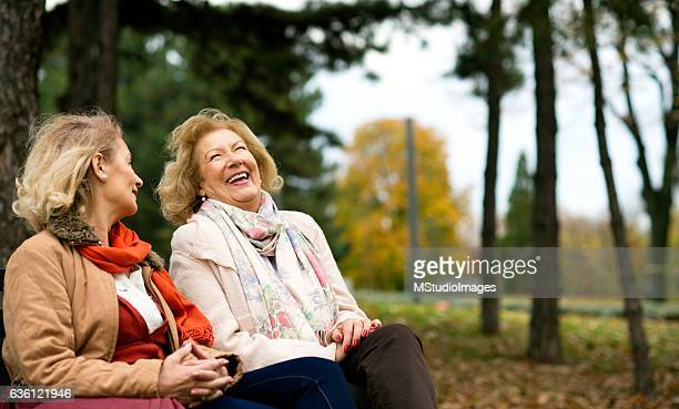Two senior friends laughing at the park.