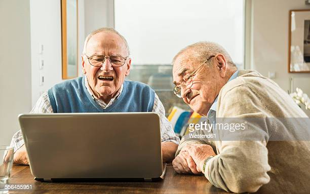Two senior friends looking at laptop