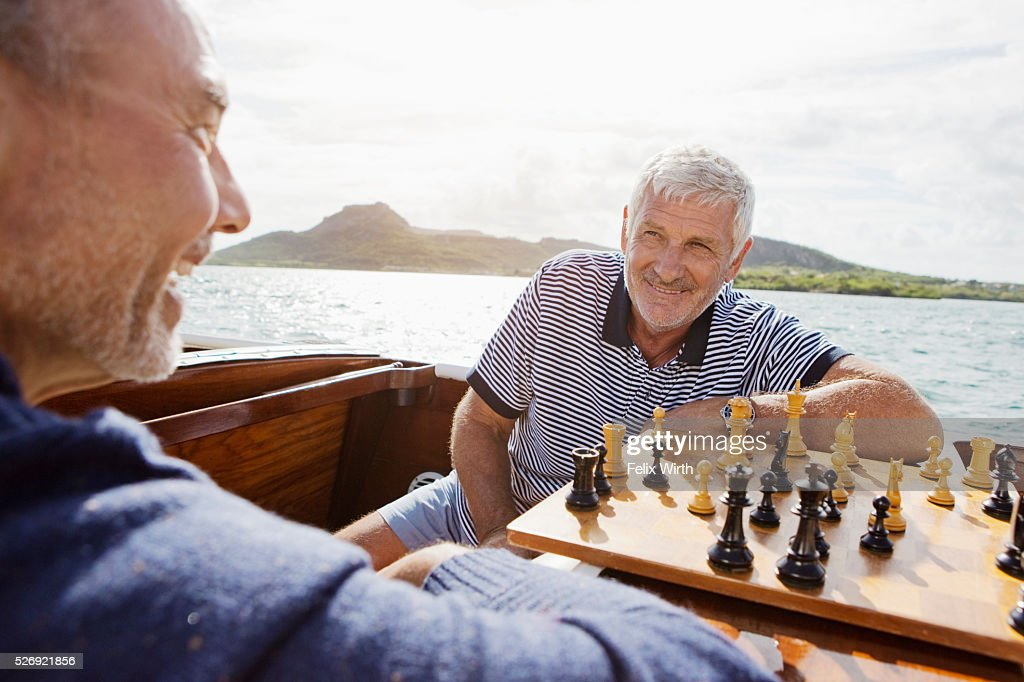 Two senior friends playing chess in motorboat : Stock Photo