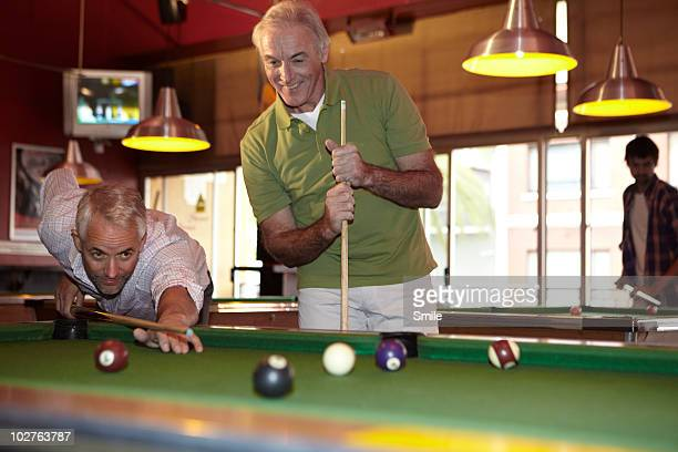 Two senior friends playing pool