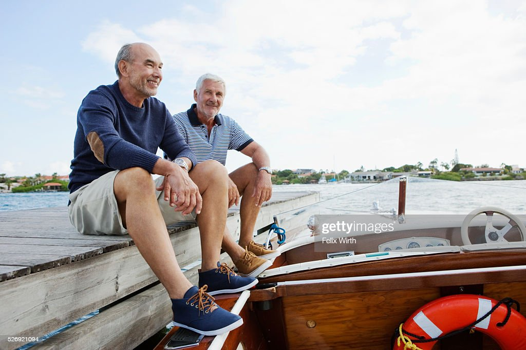 Two senior friends resting on jetty with moored motorboat : Stock Photo