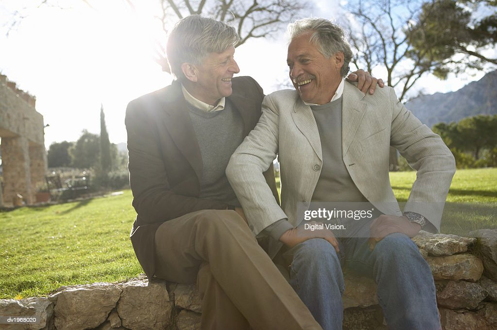 Two Senior Friends Sitting Side by Side on a Stone Wall : Stock Photo