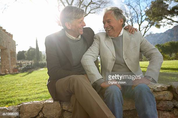 two senior friends sitting side by side on a stone wall - only senior men stock pictures, royalty-free photos & images