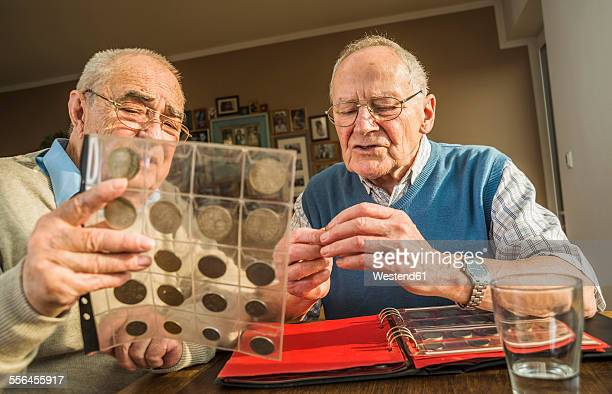two senior friends with coin album - collection stock pictures, royalty-free photos & images