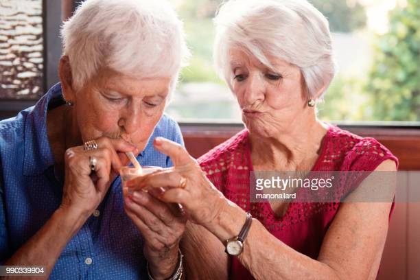 two senior girlfriends 83 years old smoke marijuana together - medical cannabis stock photos and pictures