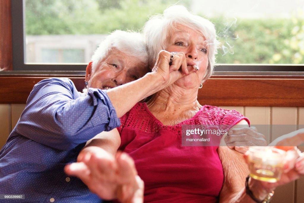 Dos amigas mayores de 83 años de edad fuman marihuana juntos : Foto de stock