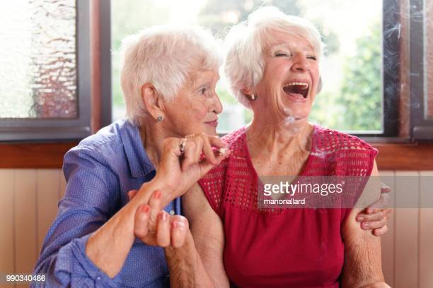 two senior girlfriends 83 years old smoke marijuana together - weed stock photos and pictures