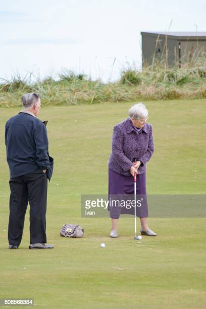 two senior golfers, couple strike a ball - セント・アンドルーズ市 ストックフォトと画像