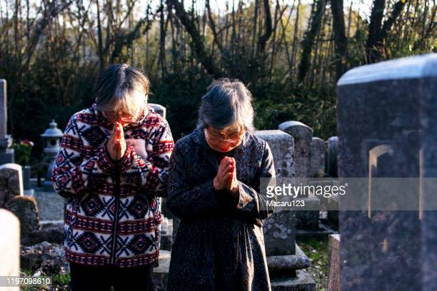 two senior japanese women put their hands together in graveyard - tomb stock pictures, royalty-free photos & images