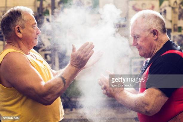 Two senior male powerlifters chalking their hands in gym