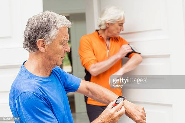 Two senior male runners at front door synchronising smartwatch and smartphone