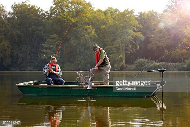 two senior man catching fish - fishing industry stock pictures, royalty-free photos & images