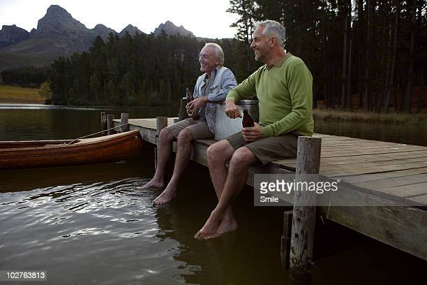 Two senior man having a beer on jetty