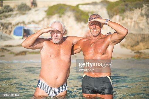 Two senior men celebrating after a swim in ocean