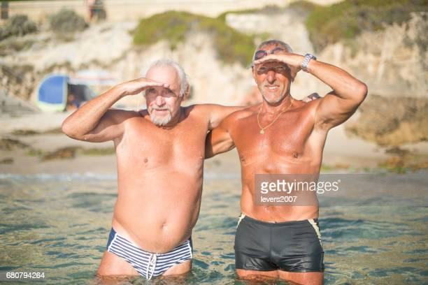Two senior men celebrating after a swim in ocean