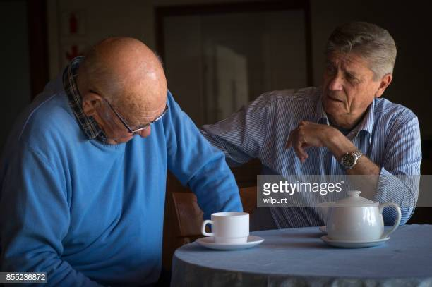 two senior men consoling one another over a cup of coffee - cancer illness stock photos and pictures