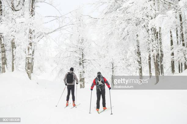 two senior men cross-country skiing in foggy weather, europe - nordic skiing event stock pictures, royalty-free photos & images