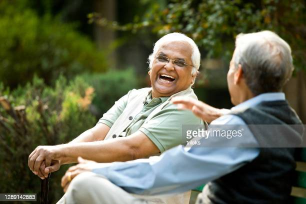two senior men discussing on park bench - senior adult stock pictures, royalty-free photos & images