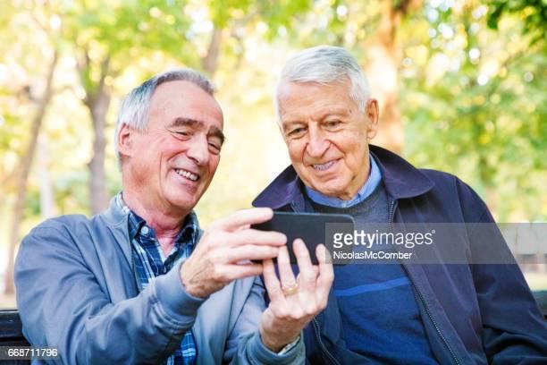 two senior men enjoying medi aon mobile phone together in park - only senior men stock pictures, royalty-free photos & images