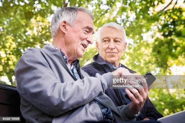twee senior mannen genieten van de tijd samen in park - alleen seniore mannen stockfoto's en -beelden