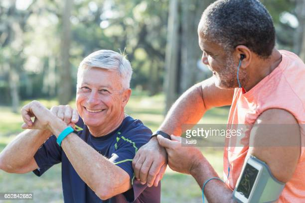 Two senior men exercising in park with fitness trackers