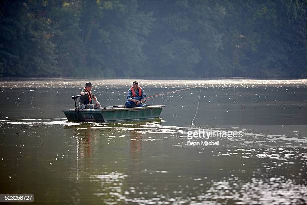 Two senior men fishing from a small boat on lake