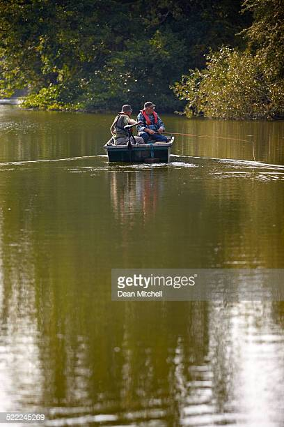 Two senior men fishing from a small boat
