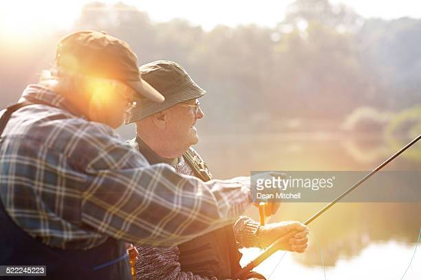 Two senior men fishing on lake