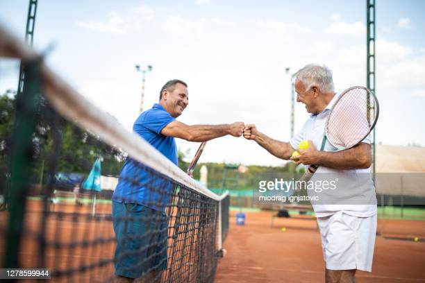 two senior men greeting each other with fist bump on tennis court - tennis player stock pictures, royalty-free photos & images