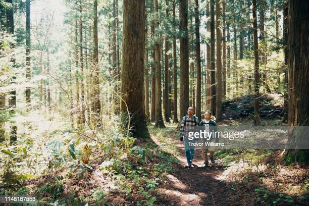Two senior men hiking together in a forest