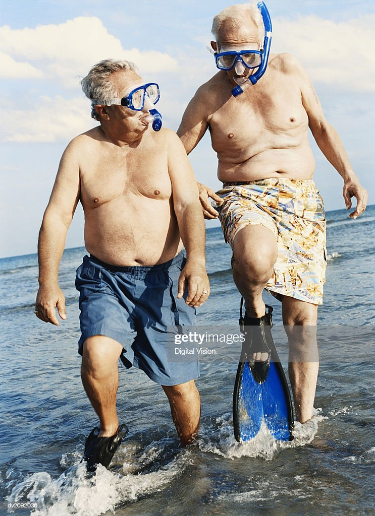 Two Senior Men in Scuba Masks and Flippers Wading in the Sea : Stock Photo